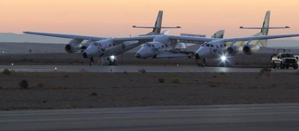 Virgin Galactic's SpaceShipTwo rocket plane is slung beneath the WhiteKnightTwo carrier plane before Friday's takeoff. Credit: Jason DiVenere / Scaled Composites